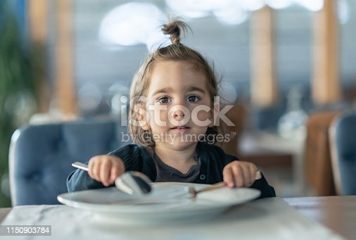Little girl holding fork and spoon with