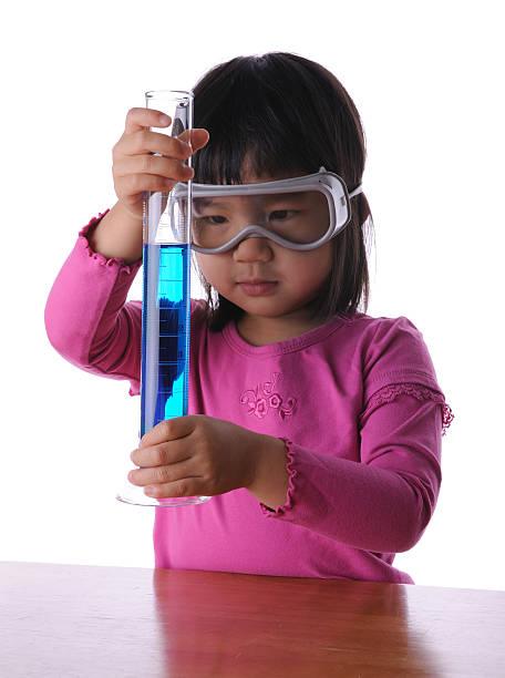 kleines mädchen hält messzylinder mit chemischen - messzylinder stock-fotos und bilder