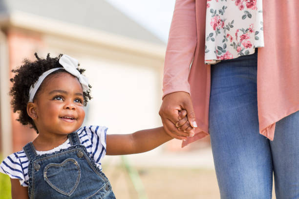 Little girl holding her mothers hand. African American little girl holding her mothers hand. sentimentality stock pictures, royalty-free photos & images