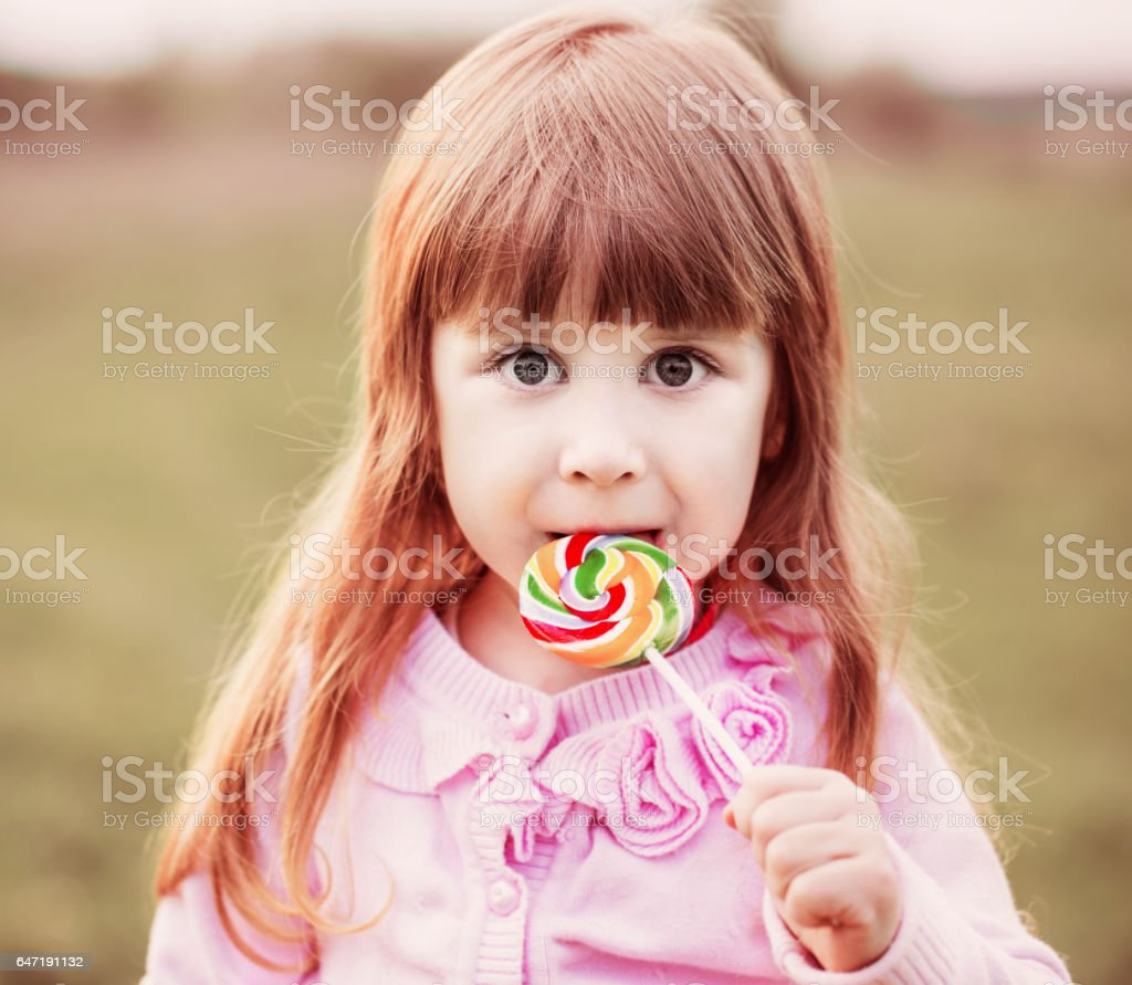 little girl  holding lollipop in her hand stock photo