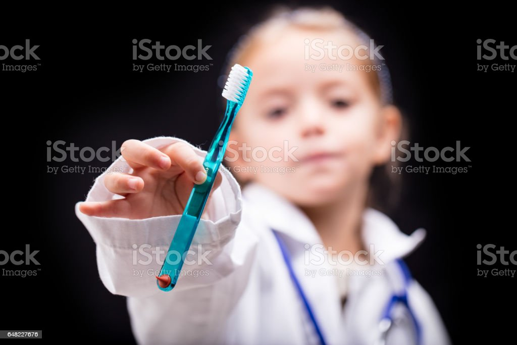 Little girl holding out a blue plastic toothbrush stock photo