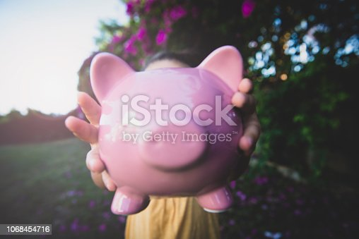 Little girl holding piggy bank at the garden.