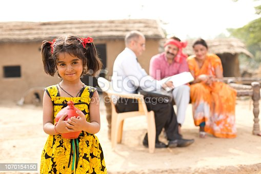 Girl holding piggy bank while parents meeting with financial advisor in the background