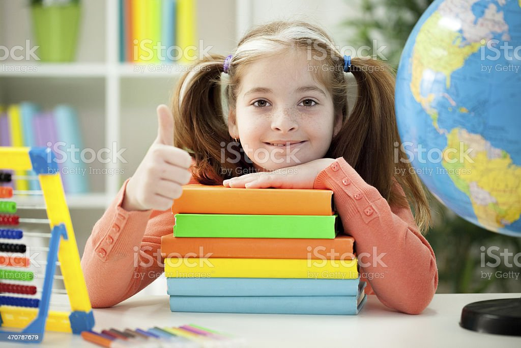 Little girl holding pile of books stock photo