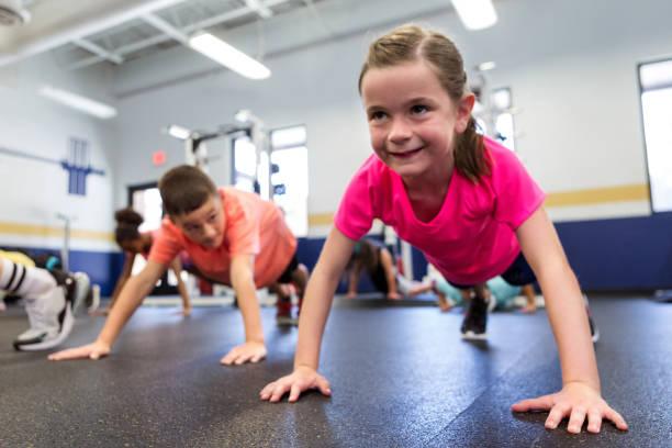 Little girl holding plank position stock photo