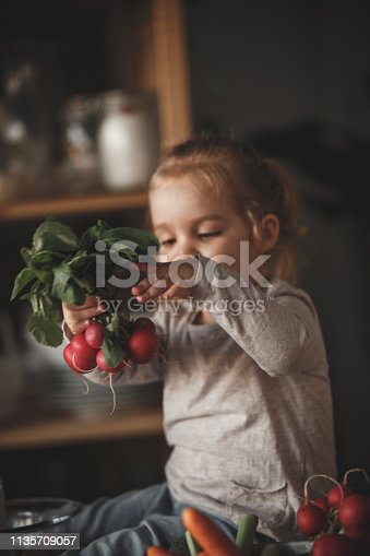 istock Little girl holding radishes in the kitchen 1135709057