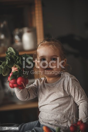 istock Little girl holding radishes in the kitchen 1135709058