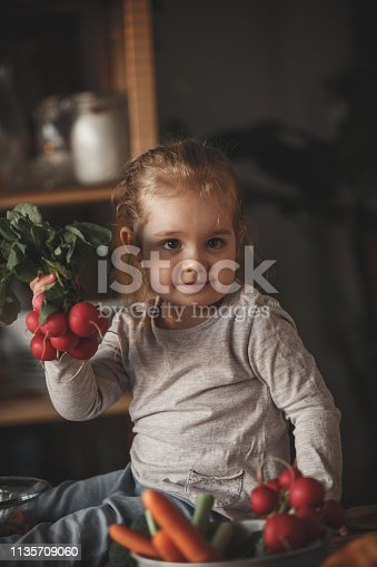 istock Little girl holding radishes in the kitchen 1135709060