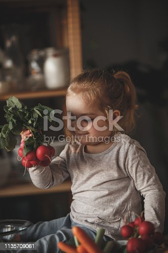 istock Little girl holding radishes in the kitchen 1135709061
