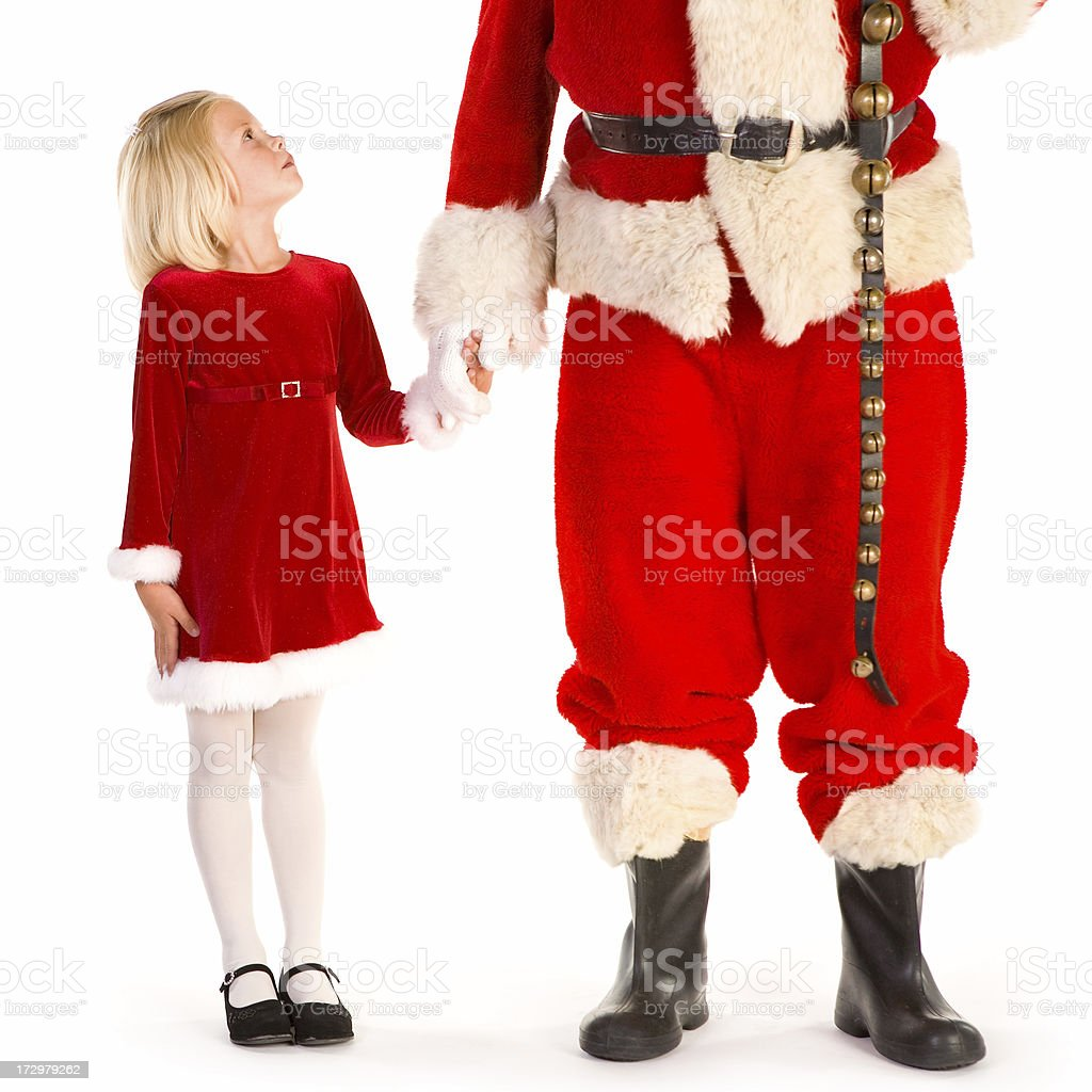Little girl holding Santa's hand looks up at him royalty-free stock photo