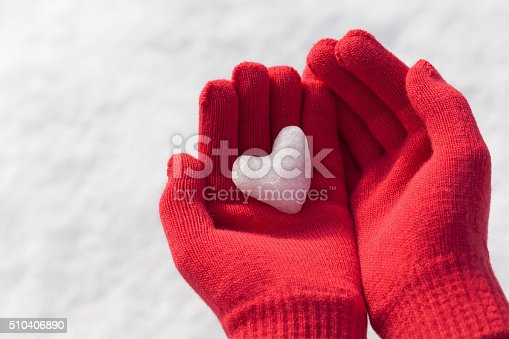 istock Little girl holding snow heart in red warm wool gloves. 510406890