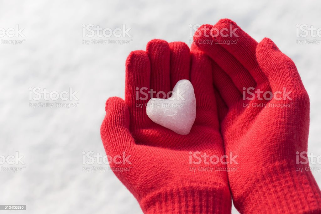 Little girl holding snow heart in red warm wool gloves. stock photo