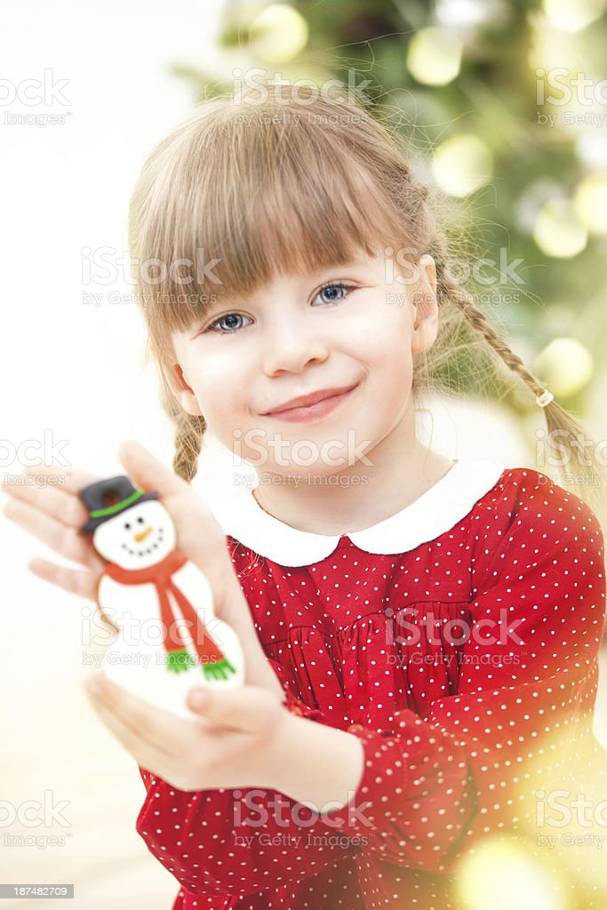 Little girl holding snowman ginger cookie stock photo