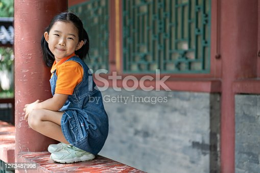 Little Girl Holding the Pillar Playing