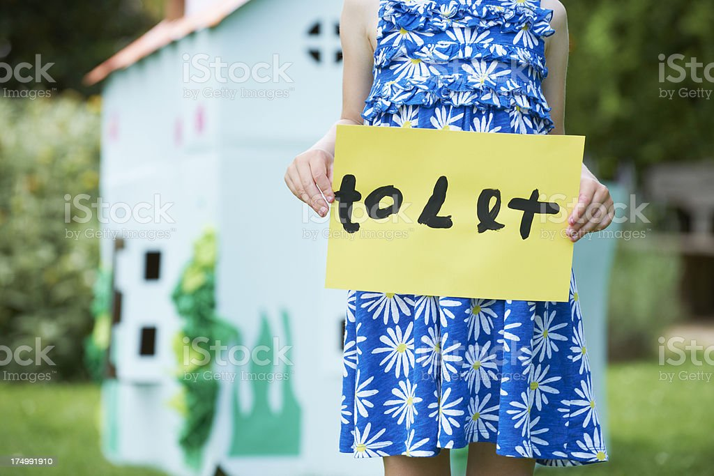 Little Girl Holding To Let Sign Outside Play House royalty-free stock photo
