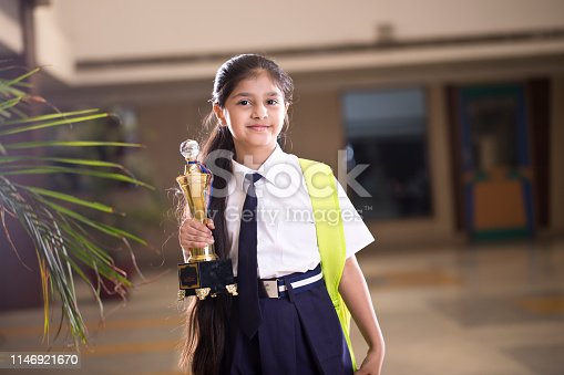 Little girl holding trophy at school campus