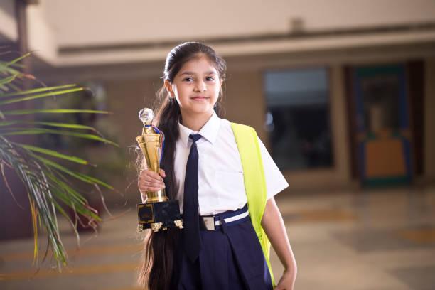 little girl holding trophy at school campus - scolara foto e immagini stock