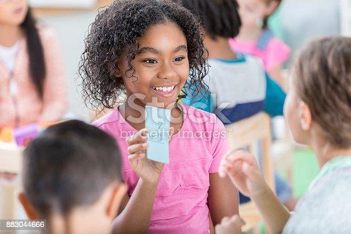 istock Little girl holds up mathematics flash card to quiz friend 883044666