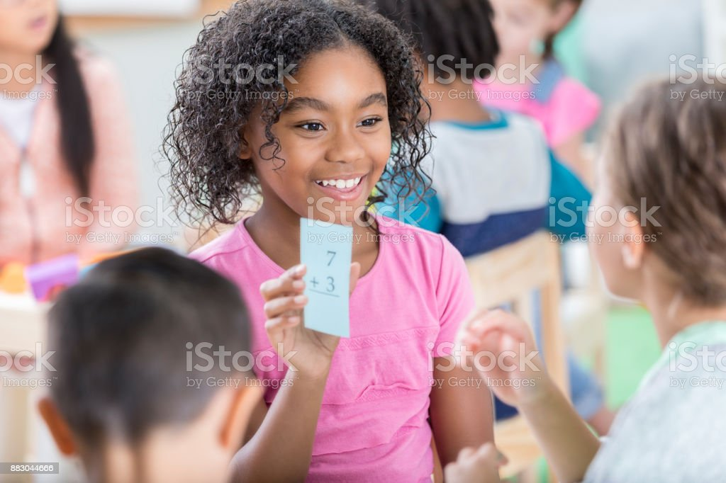 Little girl holds up mathematics flash card to quiz friend stock photo