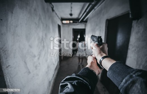 Scary girl in night gown in front of a man holding a gun