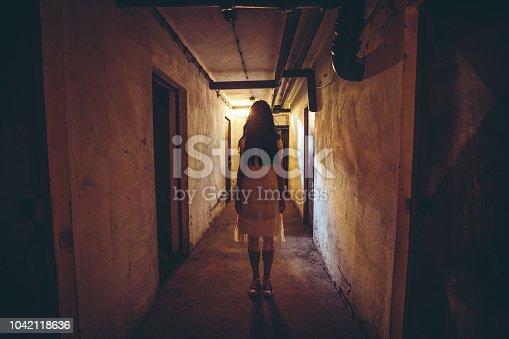 Scary girl in night gown in a dark basement hallway