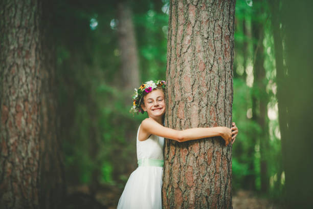 little girl hugging a tree little girl hugging a tree with a toothy smile. nature is our friend. tree hugging stock pictures, royalty-free photos & images