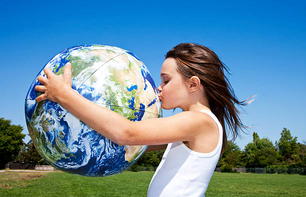 little girl hugging and kissing the globe stock photo