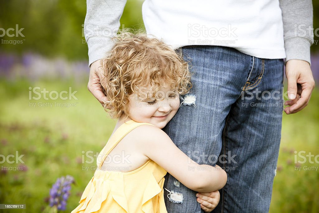Little girl hugging father's leg. royalty-free stock photo