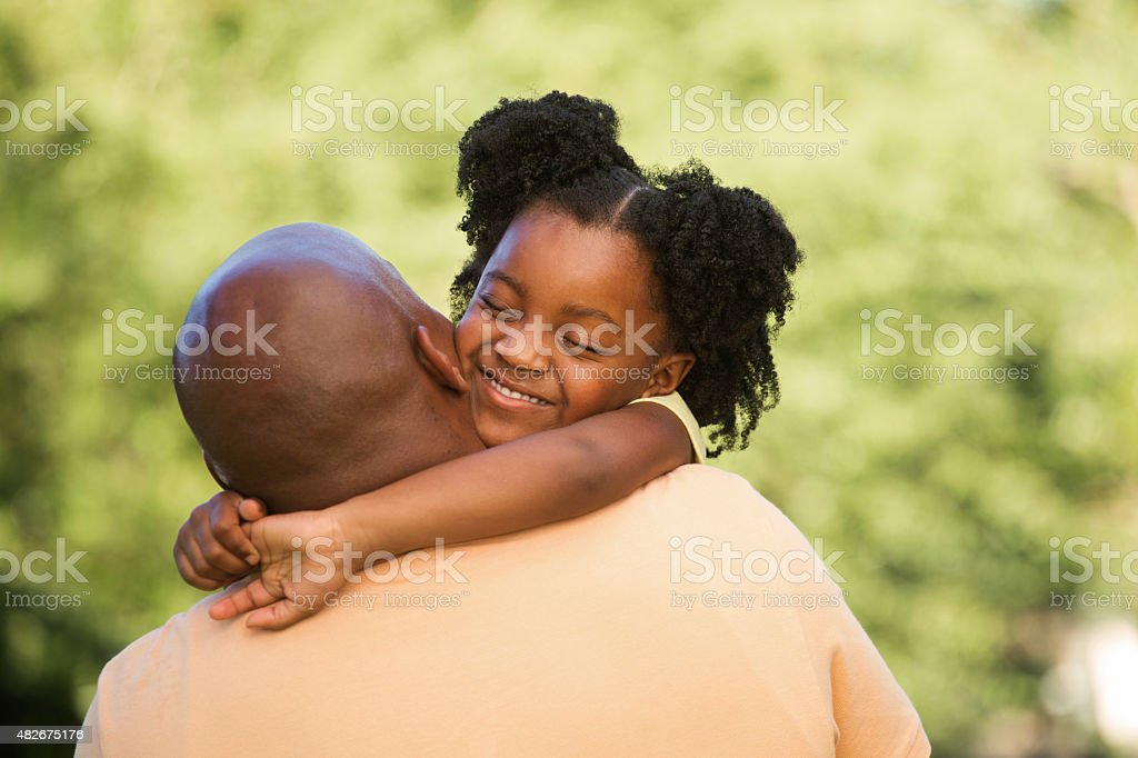 Little girl hugging her dad. stock photo