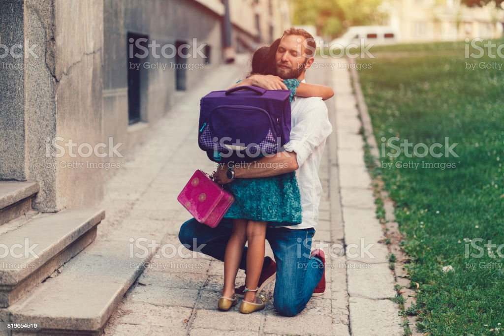 Little girl hugging her father before going to school stock photo