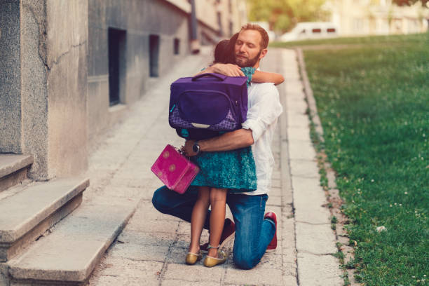 kleine mädchen ihren vater umarmt, bevor sie zur schule gehen - taschen von liebeskind stock-fotos und bilder