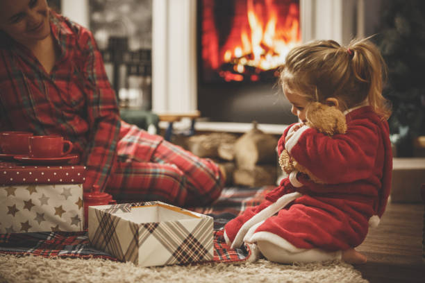Little girl hugging her new teddy bear on a Christmas Eve Little girl and her mother in pajamas are opening presents on floor of the living room. The girl is hugging her new teddy bear. christmas teddy bear stock pictures, royalty-free photos & images