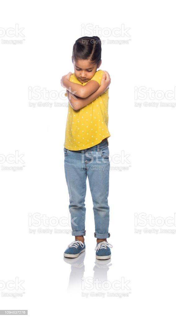 Little girl hugging herself stock photo