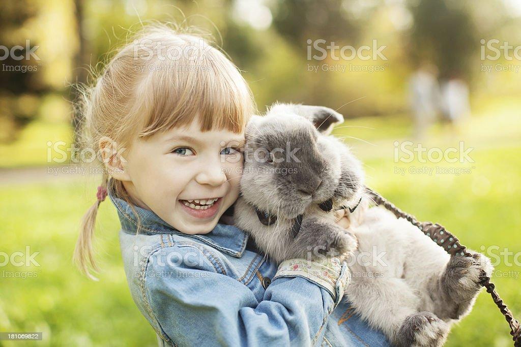 Little girl hugs a rabbit stock photo