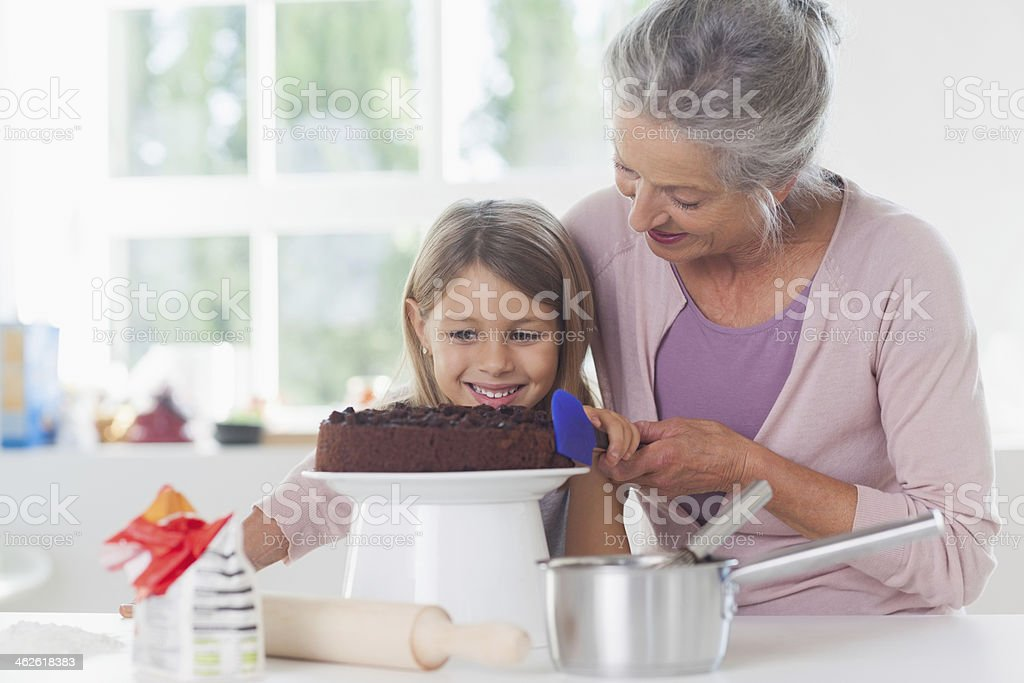 Little girl icing cake with granny royalty-free stock photo