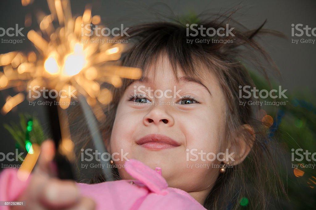 Little girl ignites sparks stock photo