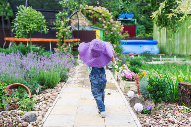 Little girl in a big violet hat walks on a flower garden. View from the back Little girl in a big violet hat walks on a flower garden. View from the back. russian dacha stock pictures, royalty-free photos & images