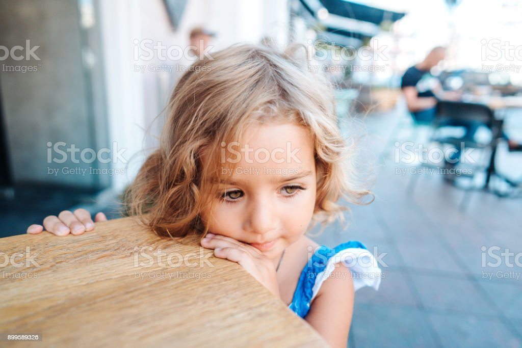Little girl in a blue dress is standing near a small table outside