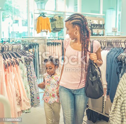 Cute 4 year old African American child in a clothing store-shopping with a parent, her smiling attractive mother