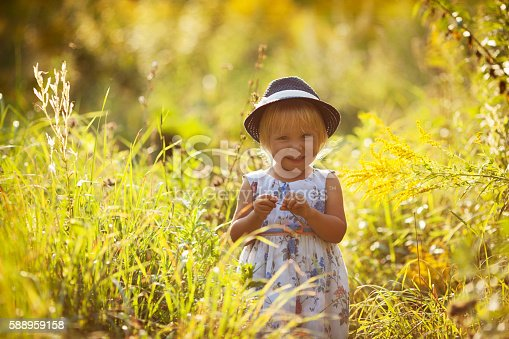 istock Little girl in a dress and hat 588959158