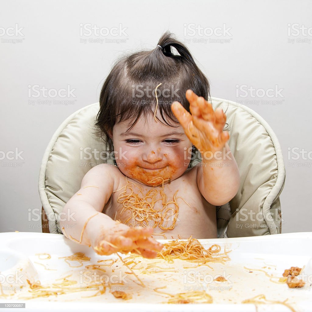 Little girl in a high chair making a mess with spaghetti royalty-free stock photo