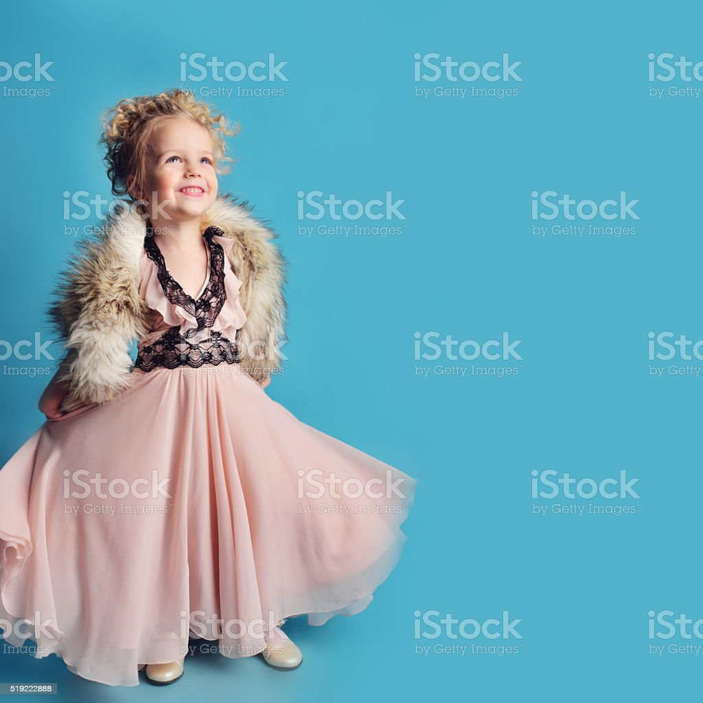 little girl in a long dress and a fur coat stock photo