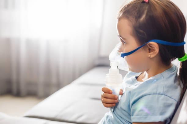 liten flicka i en mask, behandlingar andnings organen med en nebulisator hemma - astmatisk bildbanksfoton och bilder
