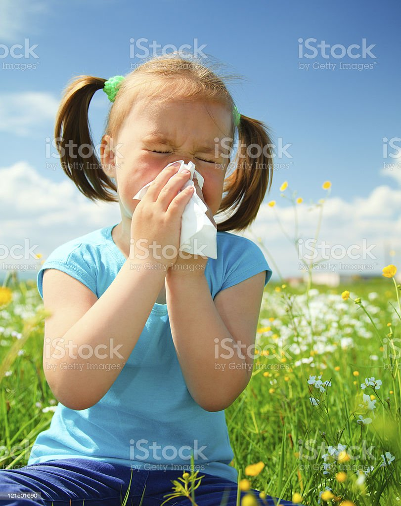 A little girl in a meadow blowing her nose stock photo