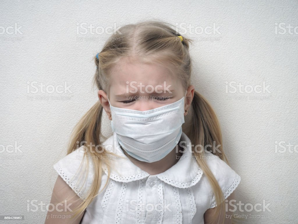 Little girl in a medical mask. Child with a sad face, closed eyes