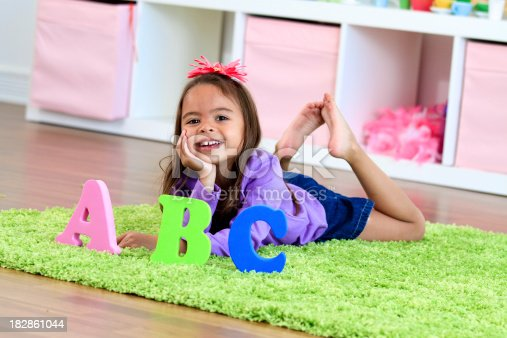 Little girl lying on the floor of a preschool room next to the letters of the alphabet.