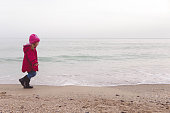little girl in a red jacket playing with the waves in cloudy weather