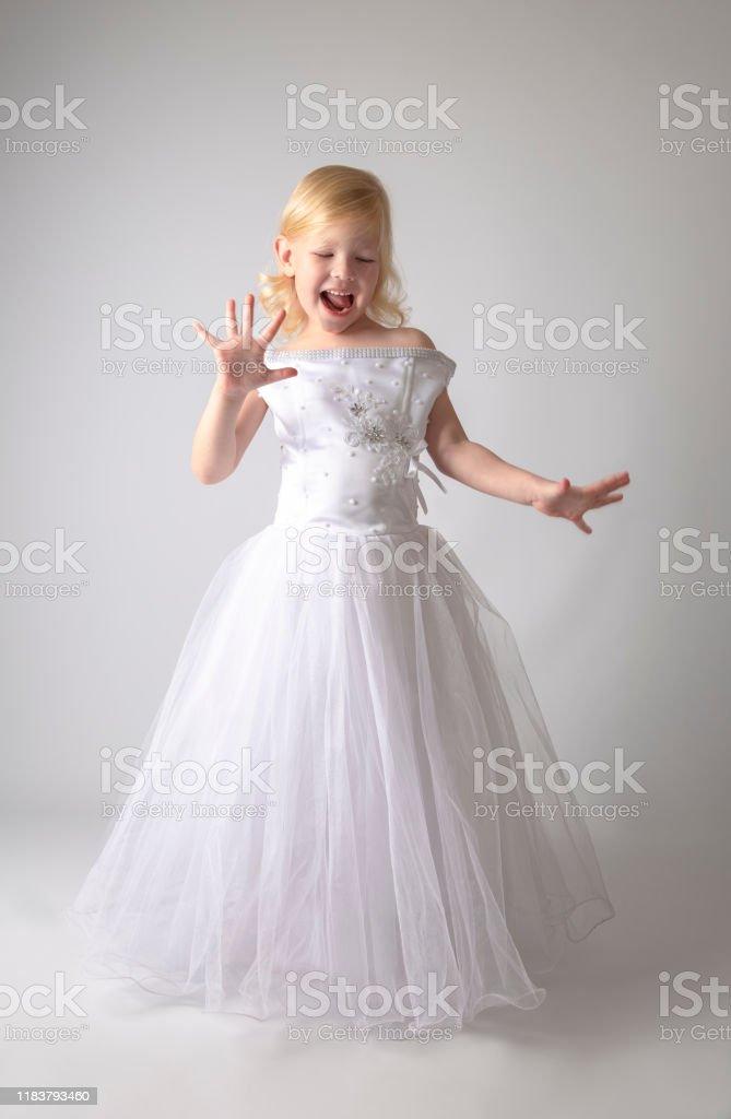 Photo Libre De Droit De Petite Fille Dans Une Robe De Mariee Jolie Petite Fille Dans La Belle Robe Blanche Disolement Sur Le Fond Leger Banque D Images Et Plus D Images Libres De