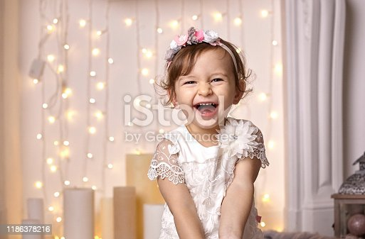 892959344 istock photo Little girl in a white dress laughs joyfully on a background of Christmas illumination 1186378216
