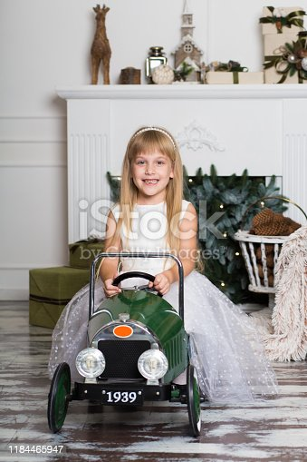 486524205 istock photo little girl in a white dress rides a vintage children's car in Christmas decorations against the background of a Christmas tree and a fireplace. Happy New year and merry Christmas 1184465947